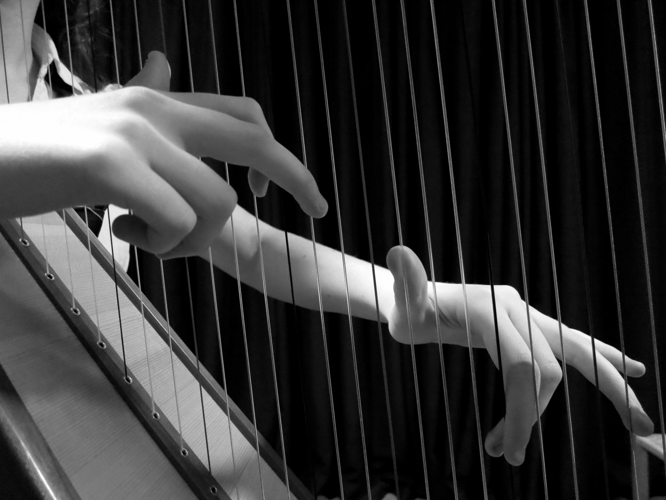 Two hands playing harp